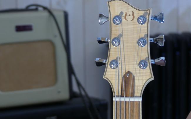 Osiris, Guitare Voyageuse et Modulaire - réalisée par Hervé BERARDET Artisan Luthier, atelier Guitare et Création - gros plan tête fond flou